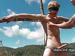 Blindfolded gay Logan Stevens bound to a cross gets