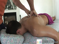 The young man with the tanned back lies on the massage table as oil is spread all over his b...