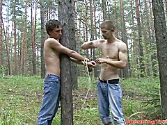 Handsome young stud is caught and tied up to a tree