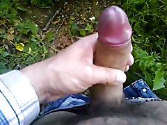 A man wank his huge thick uncut cock outdoors.
