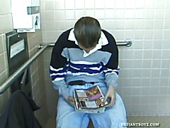 In the mens room, Christian unpacks a stack of porn