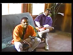 The black gay guys relax on the couch and slowly